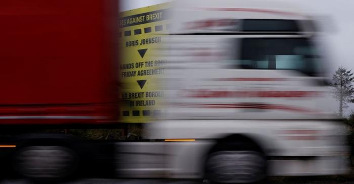A lorry passes a Brexit themed poster on the road close to the border between Northern Ireland