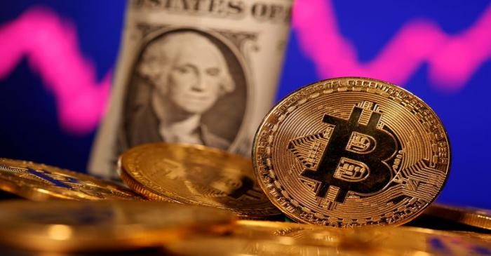 FILE PHOTO: A representation of virtual currency Bitcoin and U.S. One Dollar banknote are seen