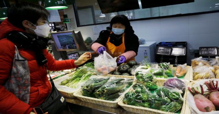 People wearing face masks shop at a market, following new cases of the coronavirus disease