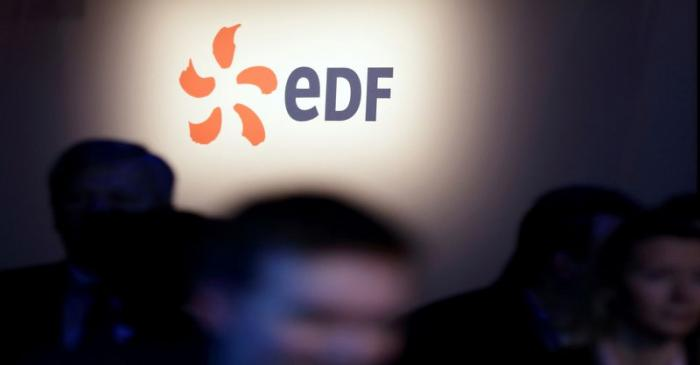 FILE PHOTO: People walk past the logo of French state-owned utility EDF during the company's