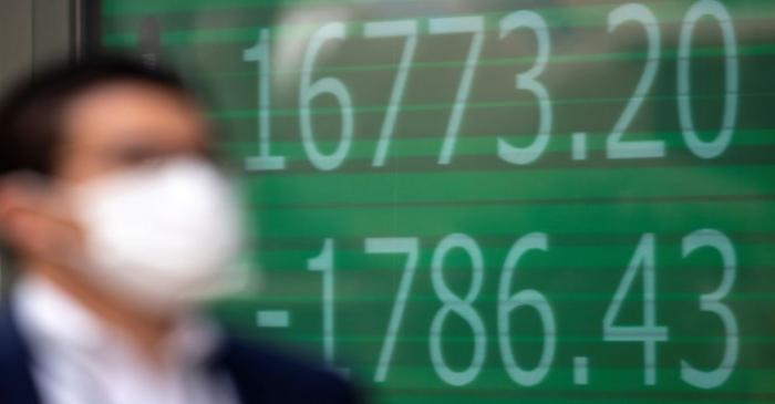 A man wearing a protective face mask walks past a screen showing Nikkei index outside a