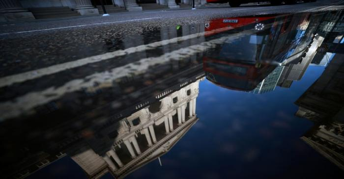 FILE PHOTO: The Bank of England and the City of London financial district are reflected in a