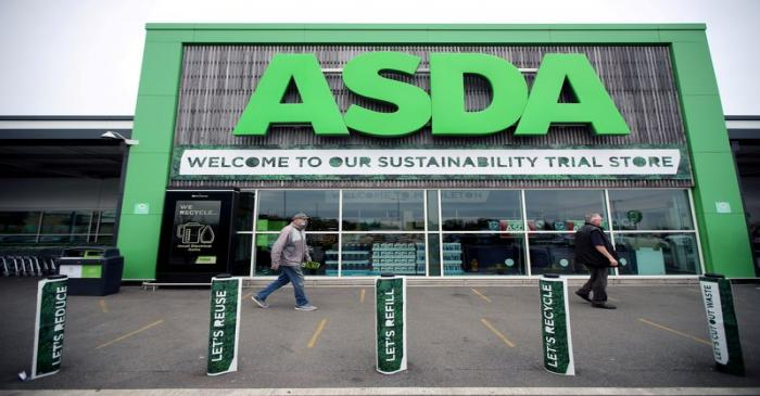 FILE PHOTO: Shoppers walk past the UK supermarket Asda, as the store launches a new