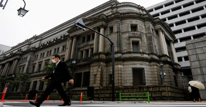 FILE PHOTO: A man wearing a protective mask walks past the headquarters of Bank of Japan amid
