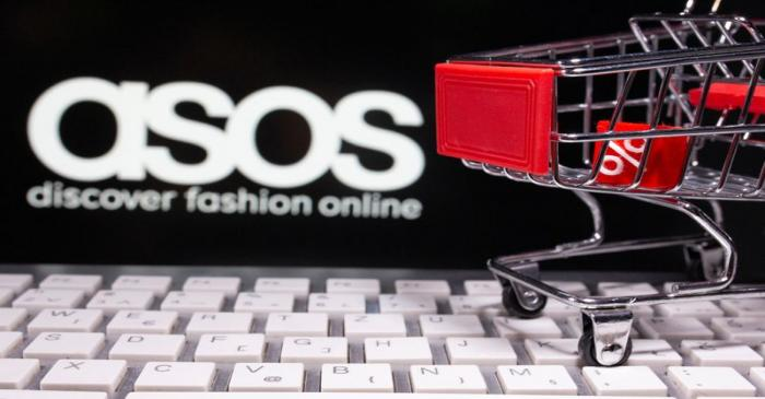 A keyboard and a shopping cart are seen in front of a displayed ASOS logo in this illustration