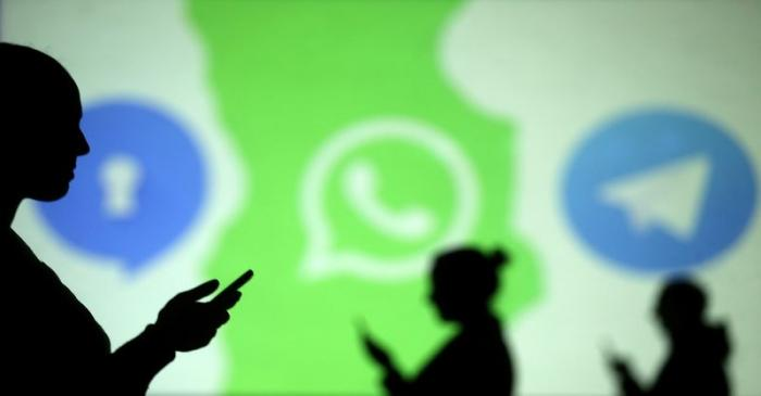 Silhouettes of mobile users are seen next to logos of social media apps Signal, Whatsapp and