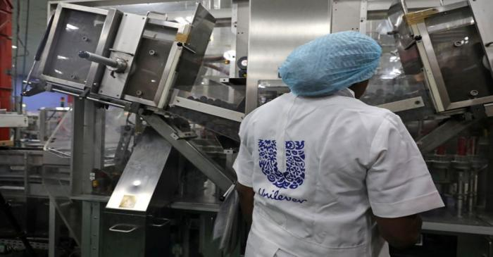 FILE PHOTO: A woman stands behind a machine that is part of a toothpaste manufacturing line at