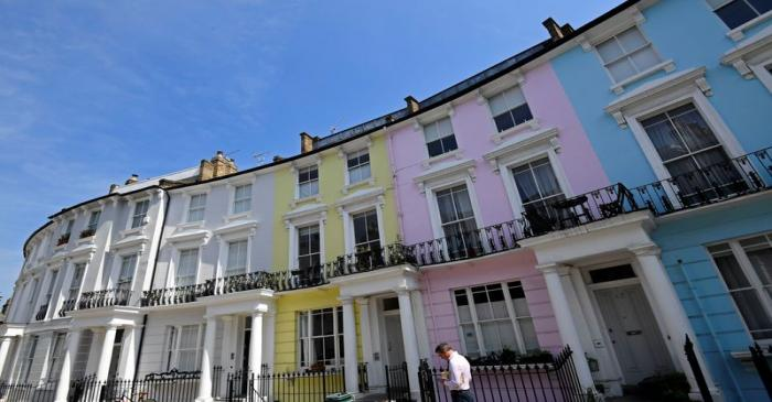 A man walks past houses painted in various colours in a residential street in London