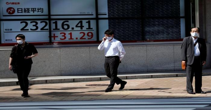 FILE PHOTO: People stand in front of a screen showing Nikkei index outside a brokerage in Tokyo