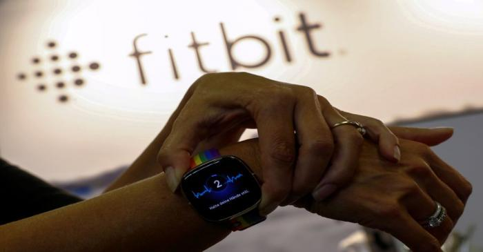 FILE PHOTO: An employee uses an electrocardiogram function on a Fitbit smartwatch at the IFA