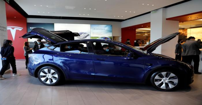 FILE PHOTO: Visitors wearing face masks check a China-made Tesla Model Y sport utility vehicle