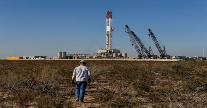 FILE PHOTO: An oil worker walks toward a drill rig in Loving County, Texas