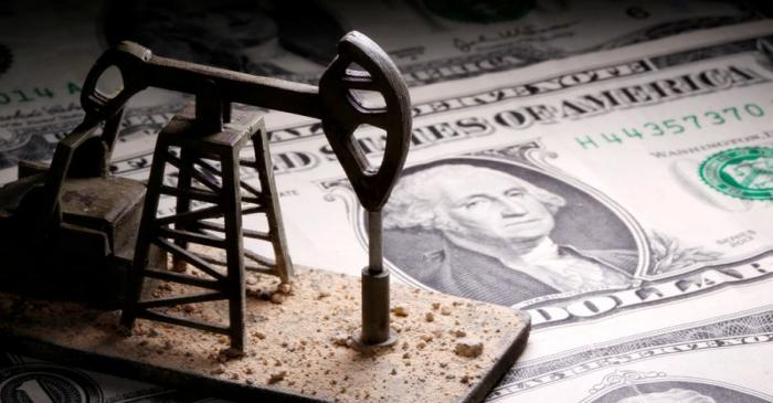 A 3D printed oil pump jack is placed on dollar banknotes in this illustration picture