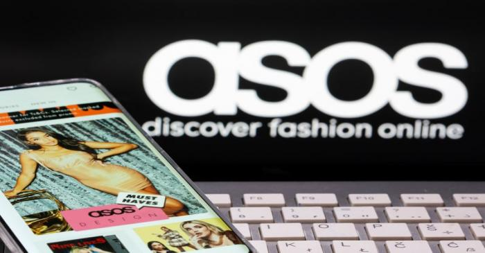 Smartphone with an ASOS app and a keyboard are seen in front of a displayed ASOS logo in this