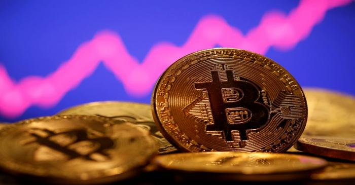 FILE PHOTO: A representation of virtual currency Bitcoin is seen in front of a stock graph in