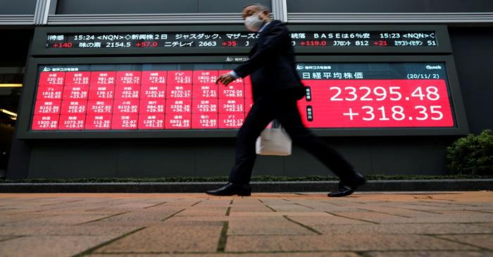A man wearing a protective face mask walks past a stock quotation board outside a brokerage,