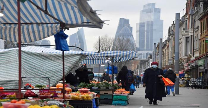 FILE PHOTO: People shop at market stalls, with skyscrapers of the CIty of London financial