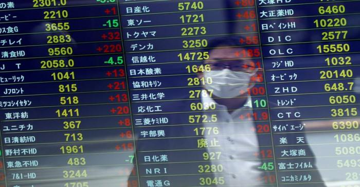 A man wearing a protective face mask is reflected on a stock quotation board at a brokerage,
