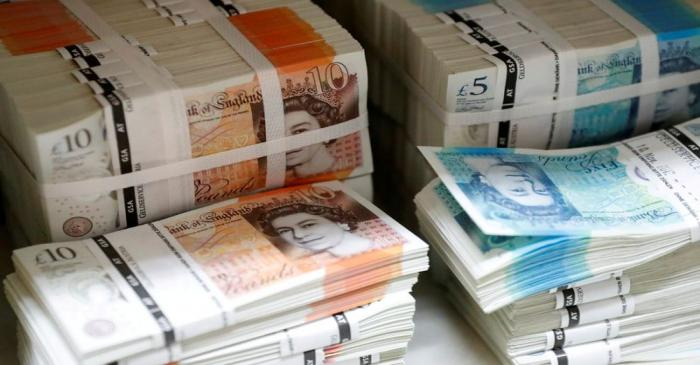 FILE PHOTO: Wads of British Pound Sterling banknotes are stacked in piles at the Money Service