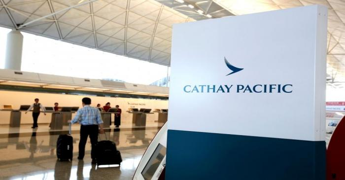 FILE PHOTO: A passenger walks to the First Class counter of Cathay Pacific Airways at Hong Kong