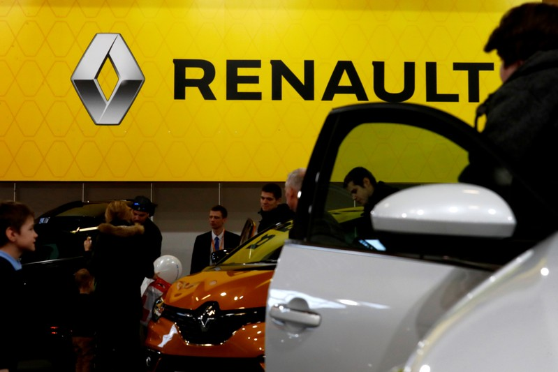 FILE PHOTO: People look on Renault cars during the international motor show Auto 2019 in Riga