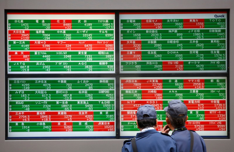 Men look at stock quotation boards outside a brokerage in Tokyo