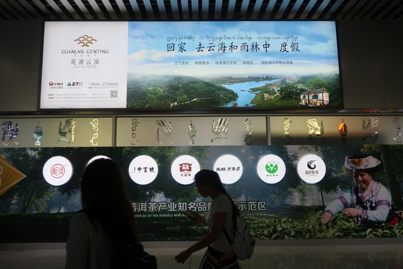 People walk past an advertisement of a property project at the airport in Xishuangbanna, Yunnan