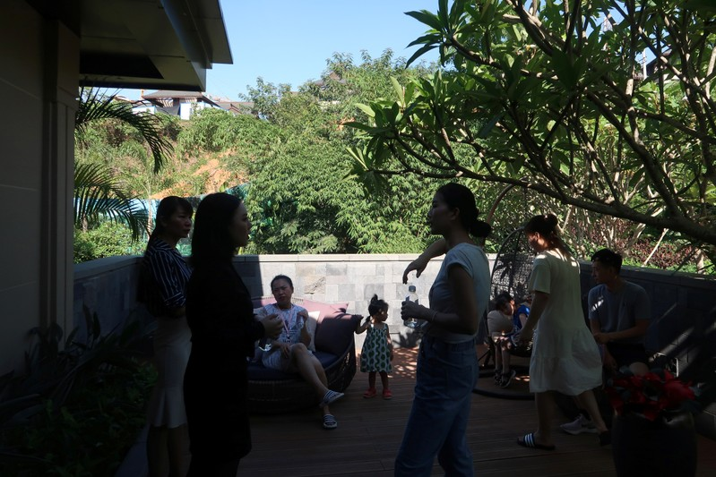 People on a property tour talk outside of a show flat at a residential property developed by