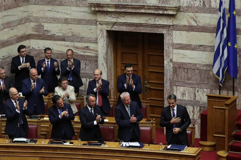 Greek PM Mitsotakis is applauded by his lawmakers and ministers after presenting his