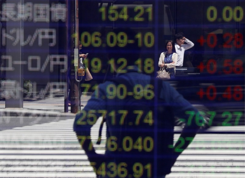 Passersby are reflected on an electronic board showing the exchange rates between the Japanese