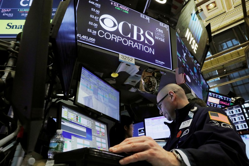 FILE PHOTO: A trader works below the CBS Corporation logo on the floor of the New York Stock
