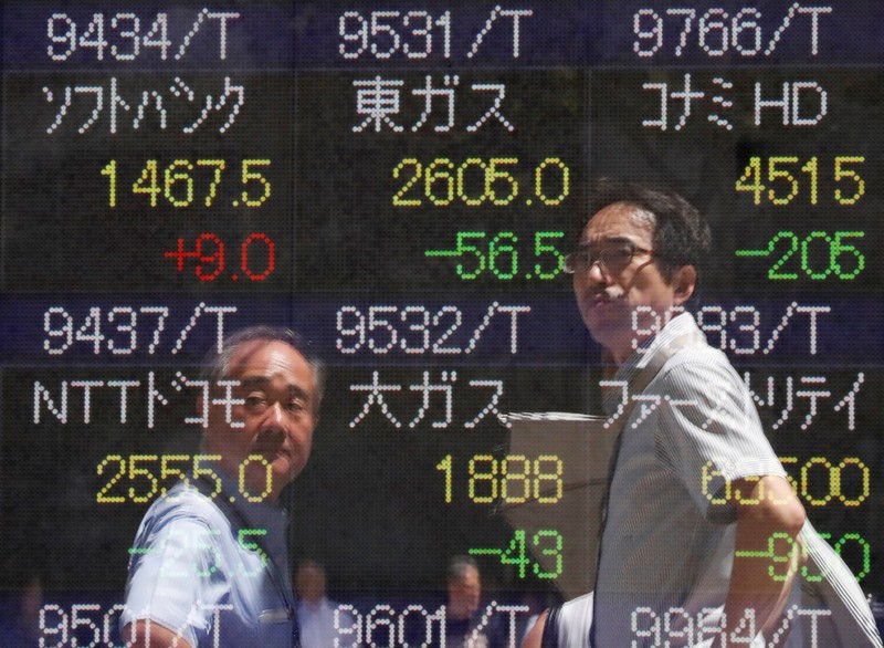 Passersby are reflected on a stock quotation board outside a brokerage in Tokyo