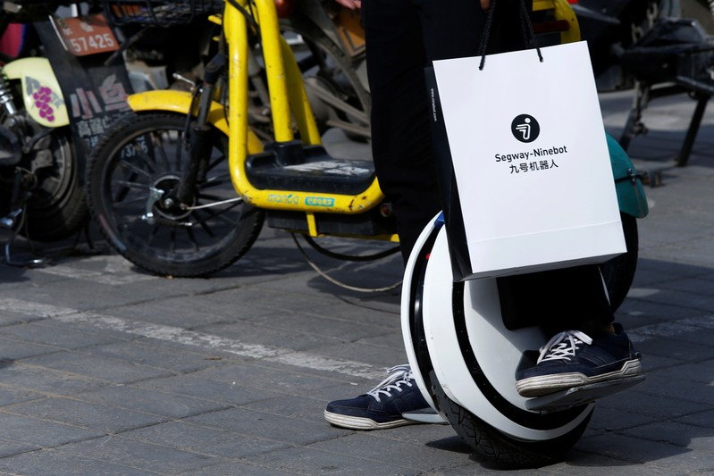 Man rides a Ninebot One electric unicycle near the venue of a Segway-Ninebot product launch
