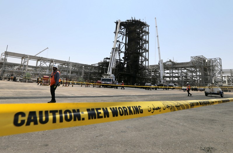 Workers are seen at the damaged site of Saudi Aramco oil facility in Khurais