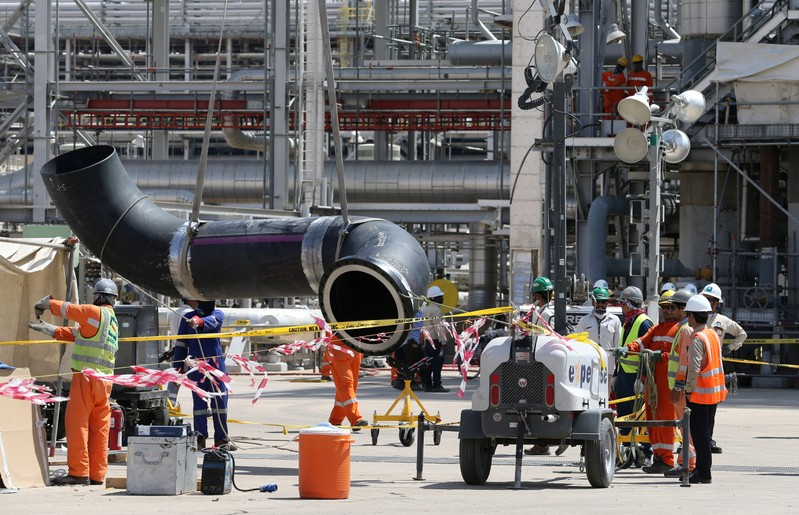 Workers fix a pipeline at the damaged site of Saudi Aramco oil facility in Khurais