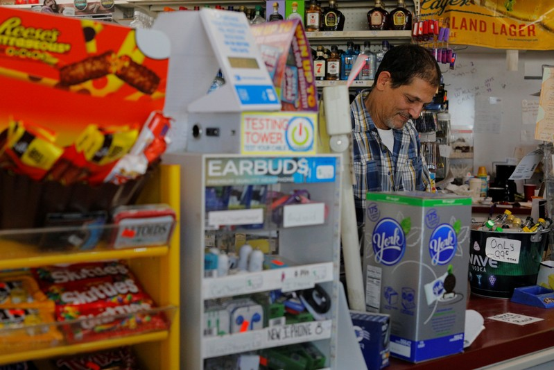 Convenience store owner Brad Khirfan stands at his counter in Flint