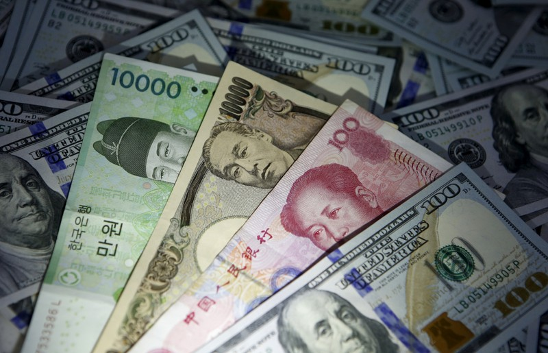 South Korean won, Chinese yuan and Japanese yen notes are seen on U.S. 100 dollar notes in this