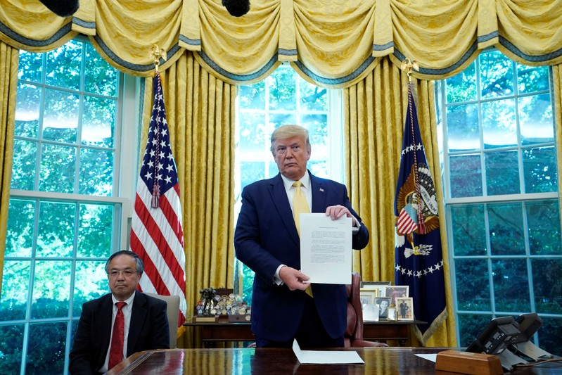 U.S. President Trump holds letter from China's President Xi Jinping during meeting with China's