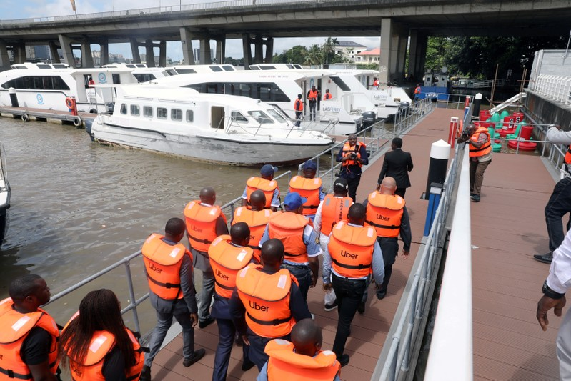 FILE PHOTO: Uber officials walk with life vests at the five cowries terminal during the