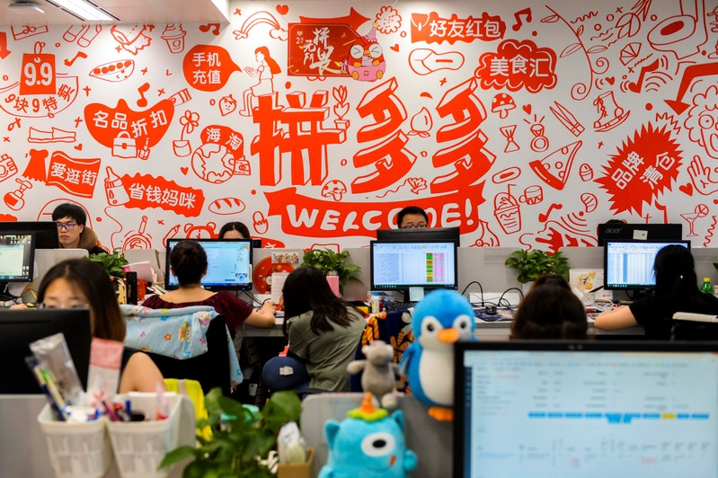 People are seen at their desks at the headquarters of Chinese online group discounter Pinduoduo