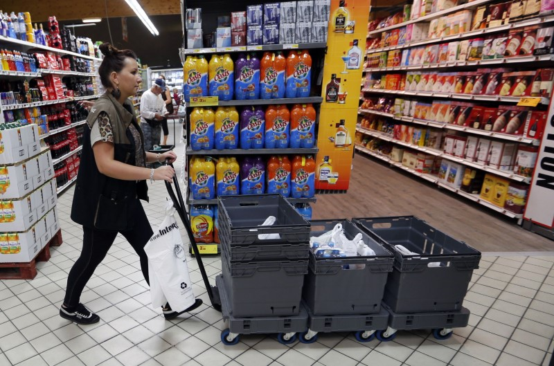 An employee pushes a caddy as she collects groceries at an Intermarche supermarket in Lanton
