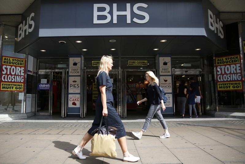 Pedestrians walk past a BHS store in London