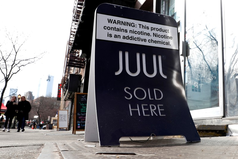 FILE PHOTO: A sign advertising Juul brand vaping products is seen outside a shop in Manhattan