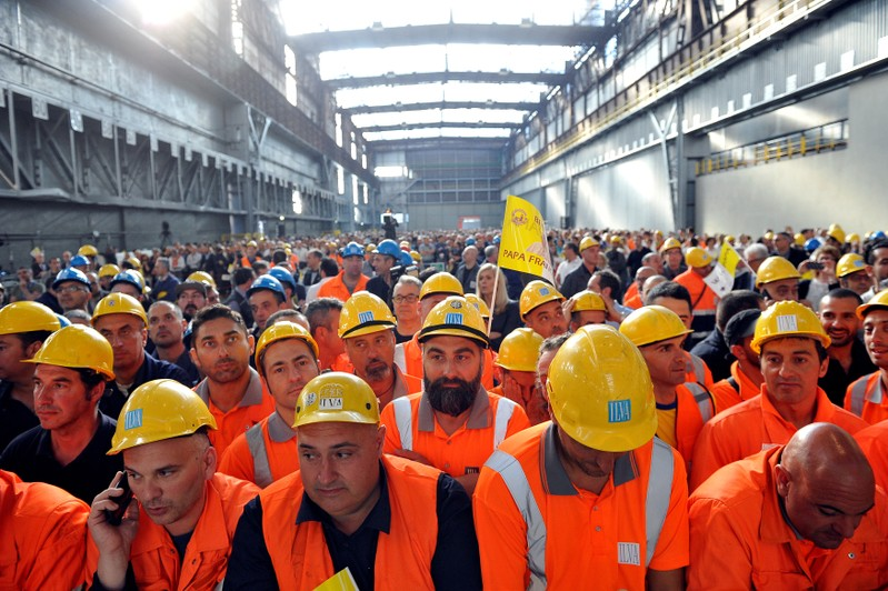 Workers from ILVA wait inside the steel plant for Pope Francis during his pastoral visit in