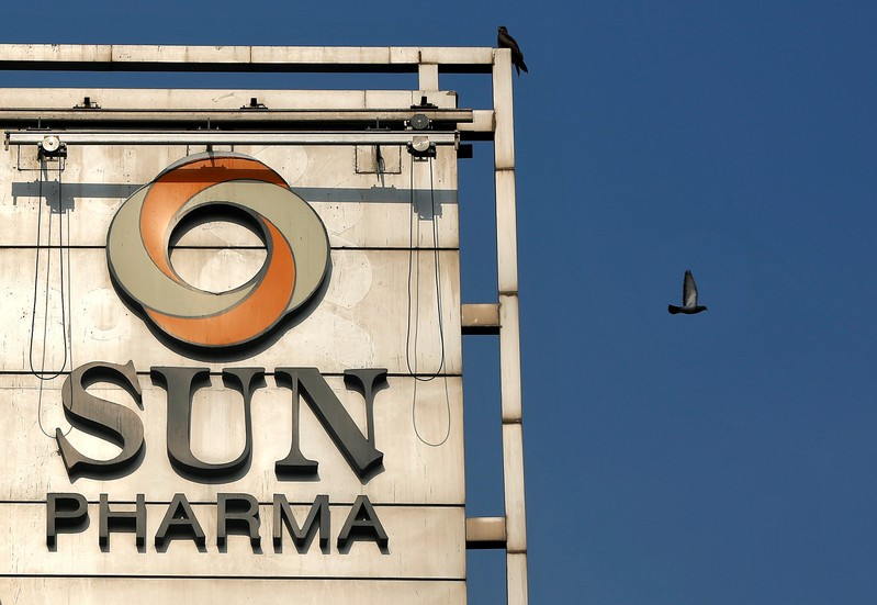 A bird flies past the logo of Sun Pharma installed on the facade of its corporate office in
