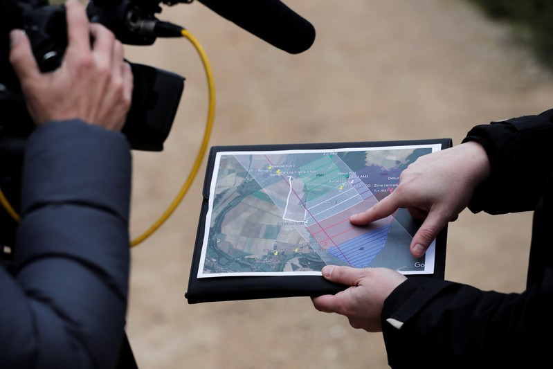 A member of the France's BEA aviation safety agency shows a map during a scour of an