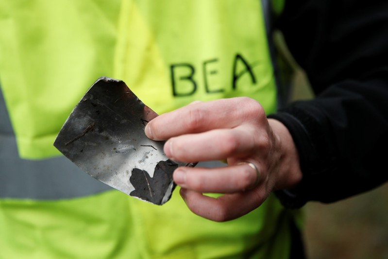A member of the France's BEA aviation safety agency holds a piece of the engine of a Swiss Air