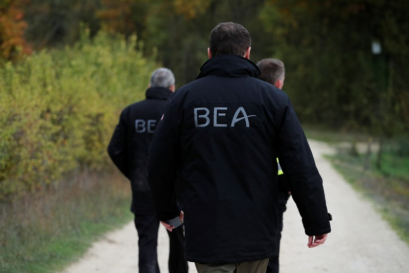 Members of the France's BEA aviation safety agency scour an uninhabited wood to find pieces of