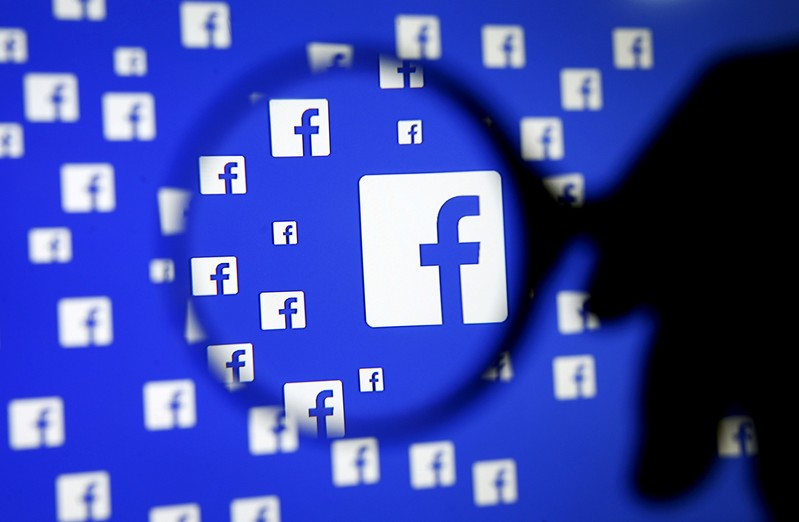 FILE PHOTO: A man poses with a magnifier in front of a Facebook logo on display in this