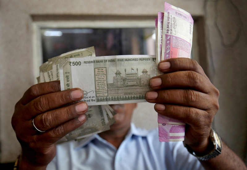 FILE PHOTO: A cashier checks Indian rupee notes inside a room at a fuel station in Ahmedabad